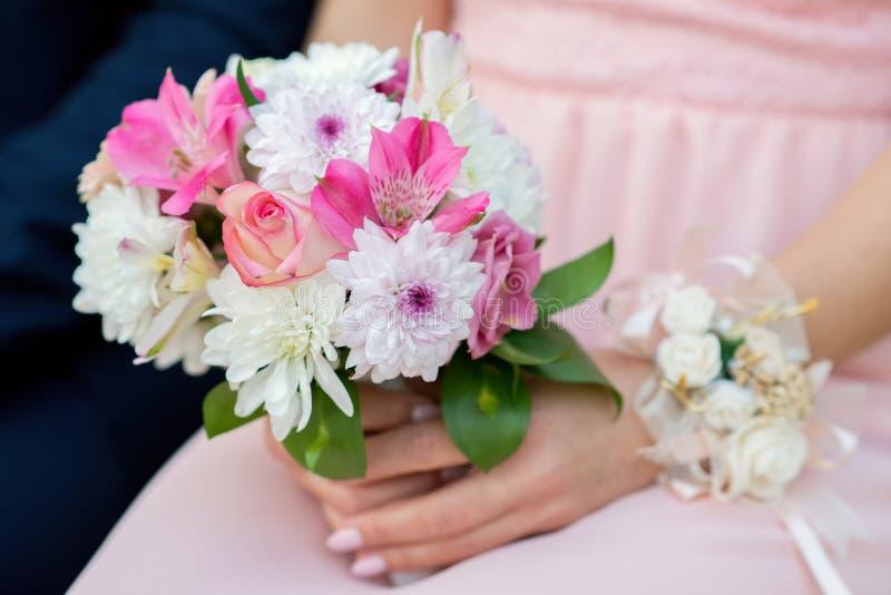 Λαμπρές παράνυμφοι στα ρόδινα φορέματα που κρατούν τα όμορφα λουλούδια στοκ εικόνες