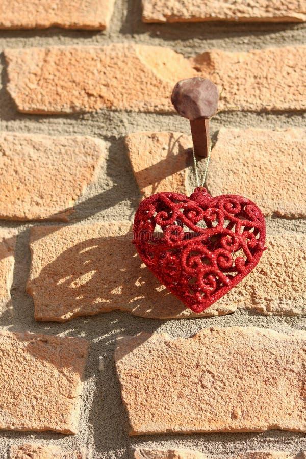 Λαμπρή κόκκινη μορφή της καρδιάς ως διακόσμηση για την ένωση Χριστουγέννων στοκ εικόνα