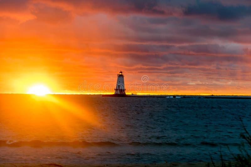 Λαμπρό ηλιοβασίλεμα πέρα από τη λίμνη πίσω από το φάρο στοκ φωτογραφίες