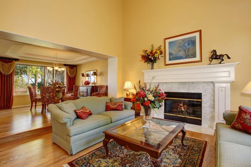 Λαμπρό καθιστικό με τους πράσινους καναπέδες, και κίτρινοι τοίχοι στοκ φωτογραφία με δικαίωμα ελεύθερης χρήσης
