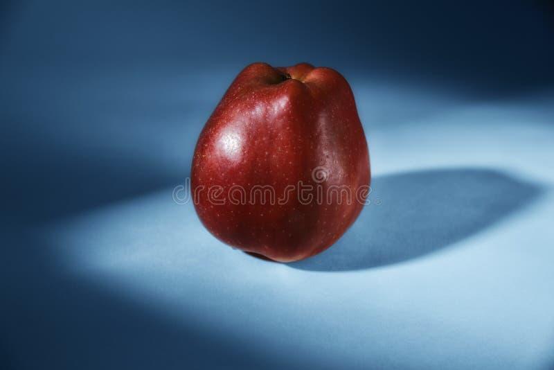 Λαμπρό κόκκινο μήλο σε ένα μπλε υπόβαθρο στοκ εικόνες