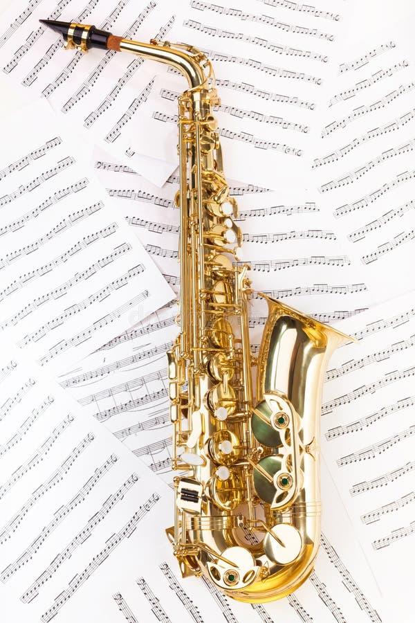 Λαμπρό saxophone alto στο πλήρες μέγεθος στις μουσικές νότες στοκ φωτογραφίες