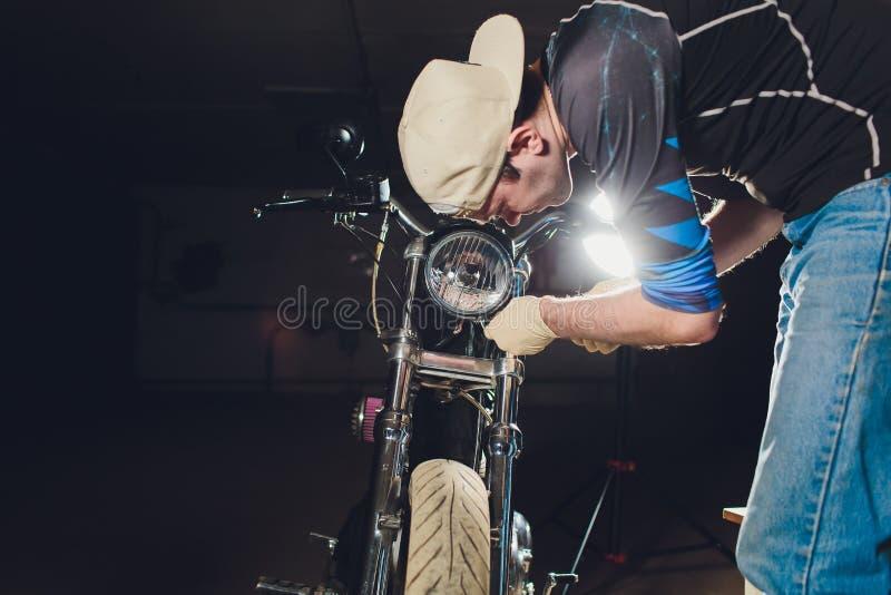Ποδήλατο καθορισμού ατόμων Βέβαιος νεαρός άνδρας που επισκευάζει τη μοτοσικλέτα κοντά στο γκαράζ του λαμπτήρας αντικατάστασης στο στοκ εικόνα με δικαίωμα ελεύθερης χρήσης