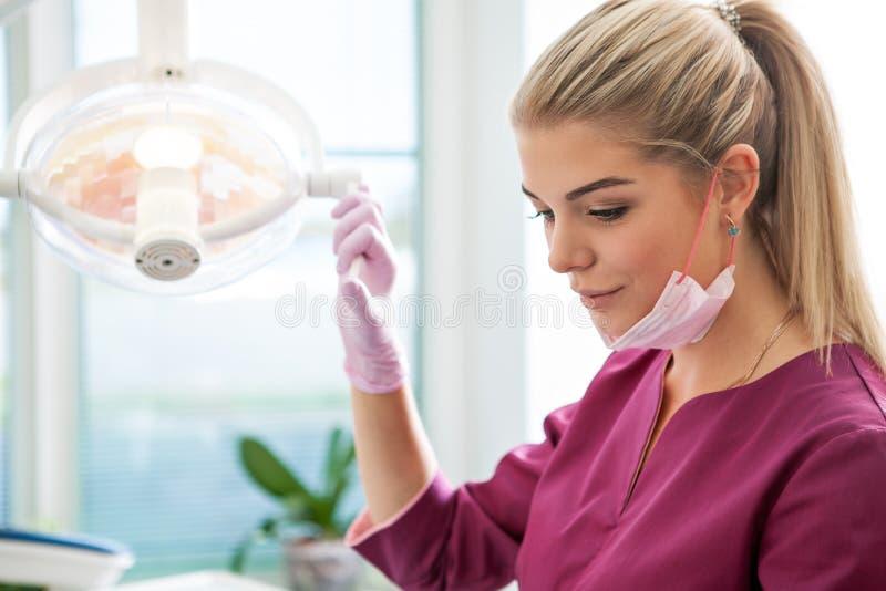 Λαμπτήρας εκμετάλλευσης οδοντιάτρων γυναικών και lookinf για έναν ασθενή στο οδοντικό γραφείο στοκ εικόνες με δικαίωμα ελεύθερης χρήσης