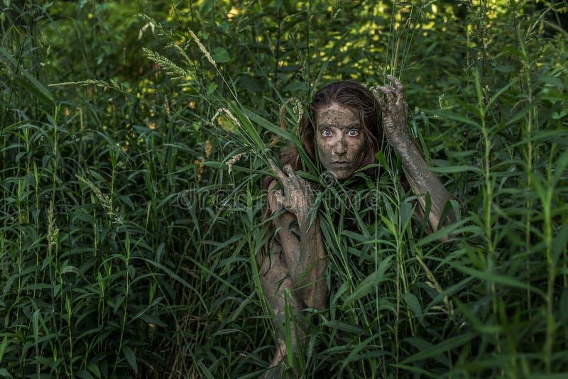 Λασπώδες κρύψιμο κοριτσιών του Αμαζονίου πίσω από έναν θάμνο στα ξύλα στοκ φωτογραφία με δικαίωμα ελεύθερης χρήσης