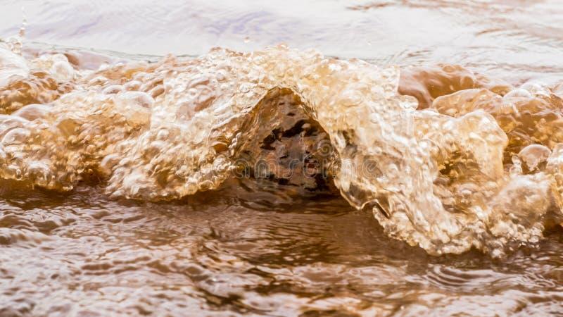 Λασπώδη κύματα νερού που χτυπούν έναν βράχο, Panshet στοκ φωτογραφίες
