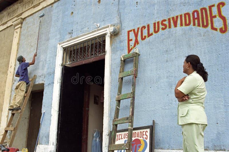 Λατίνα γυναίκα για να ελέγξει την εργασία του άνδρα ζωγράφος στοκ φωτογραφία με δικαίωμα ελεύθερης χρήσης
