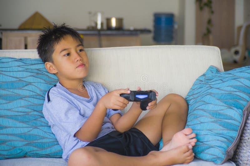 Λατινικός νεαρός 8 χρονών συγκινημένος και ευτυχής παίζοντας τηλεοπτικός μακρινός ελεγκτής εκμετάλλευσης παιχνιδιών σε απευθείας  στοκ εικόνα με δικαίωμα ελεύθερης χρήσης