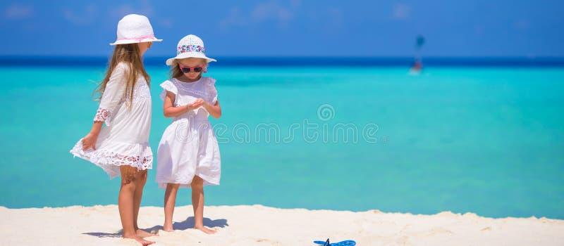 Λατρευτά μικρά κορίτσια που έχουν τη διασκέδαση κατά τη διάρκεια της παραλίας στοκ εικόνες