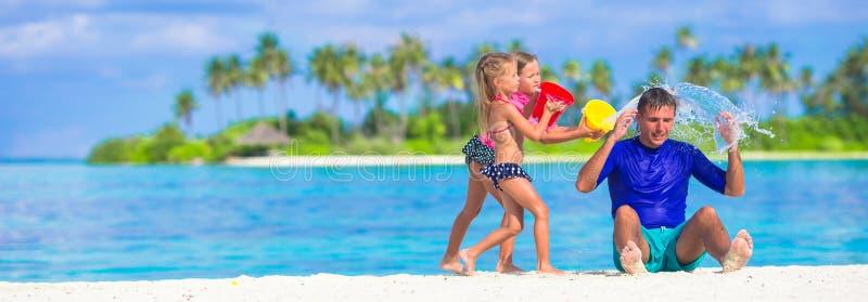 Λατρευτά μικρά κορίτσια που έχουν τη διασκέδαση με τον μπαμπά στο λευκό στοκ εικόνα