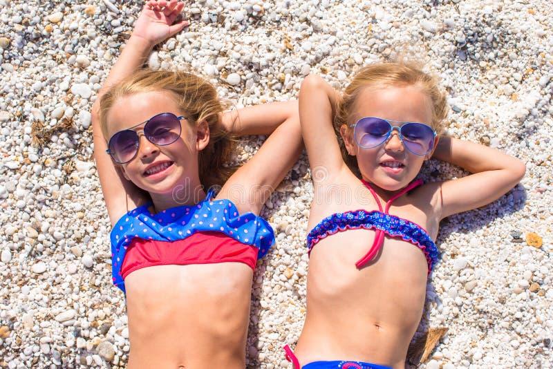 Λατρευτά μικρά κορίτσια στην παραλία κατά τη διάρκεια του καλοκαιριού στοκ φωτογραφία με δικαίωμα ελεύθερης χρήσης