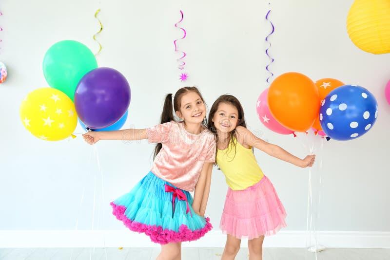Λατρευτά μικρά κορίτσια στη γιορτή γενεθλίων στο εσωτερικό στοκ φωτογραφία