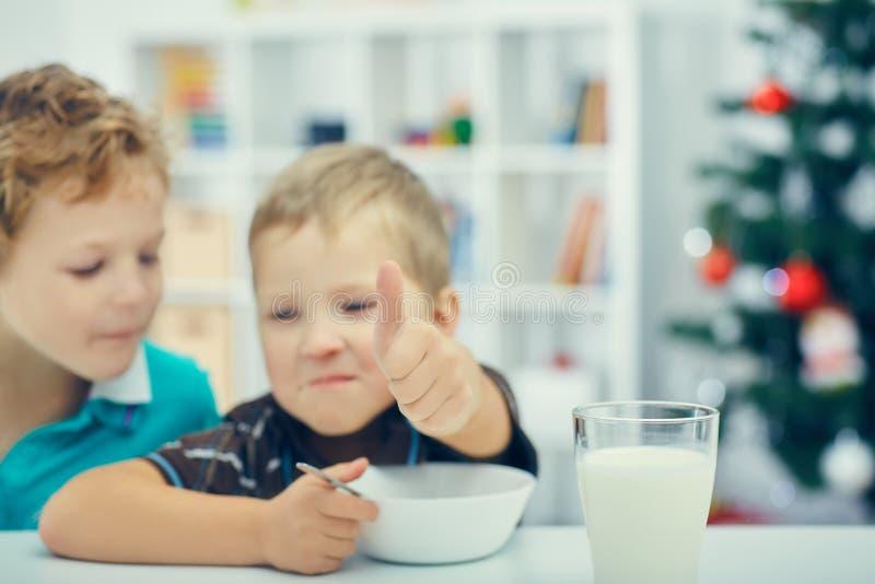 Λατρευτά μικρά ξανθά παιδιά που τρώνε τα δημητριακά για το πρόγευμα ή το μεσημεριανό γεύμα στοκ φωτογραφίες