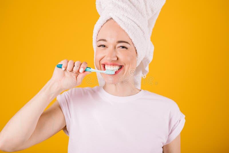 Λατρευτά νέα δόντια βουρτσίσματος γυναικών Κίτρινη ανασκόπηση Άσπρη πετσέτα στην επικεφαλής και άσπρη μπλούζα στοκ φωτογραφία με δικαίωμα ελεύθερης χρήσης