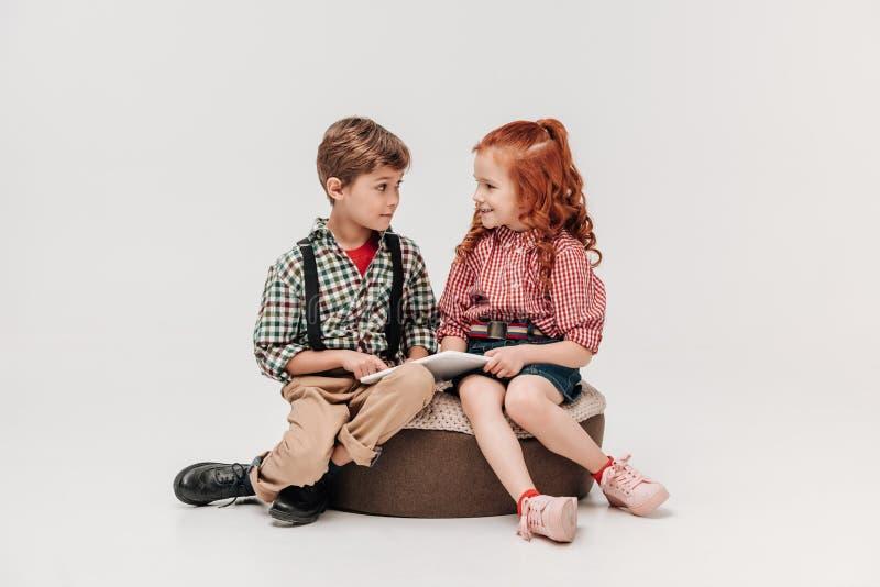 λατρευτά παιδιά που χαμογελούν το ένα το άλλο χρησιμοποιώντας την ψηφιακή ταμπλέτα στοκ φωτογραφία με δικαίωμα ελεύθερης χρήσης