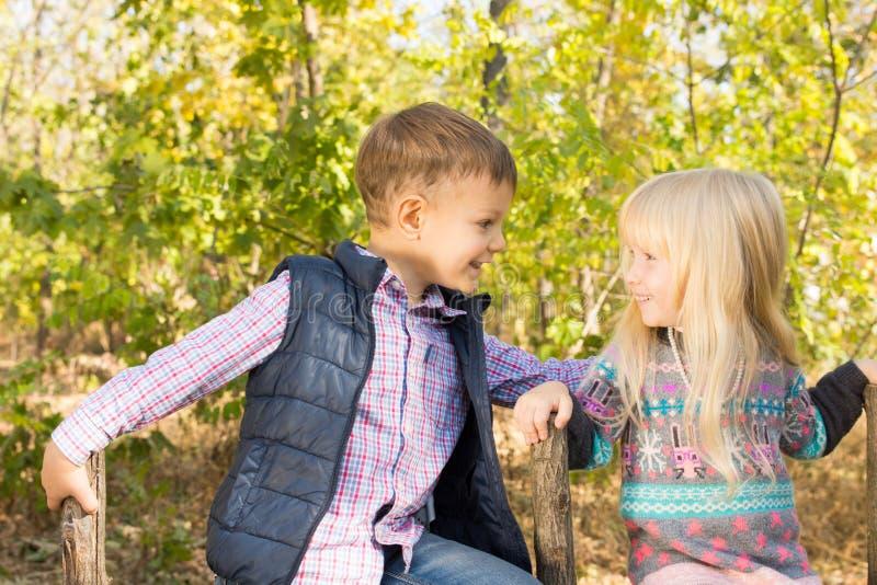 Λατρευτά παιδιά που χαμογελούν μεταξύ τους στο πάρκο στοκ φωτογραφίες με δικαίωμα ελεύθερης χρήσης