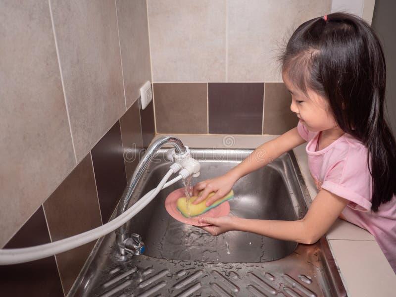 Λατρευτά πιάτα πλύσης κοριτσιών παιδιών στην εσωτερική κουζίνα στοκ φωτογραφίες