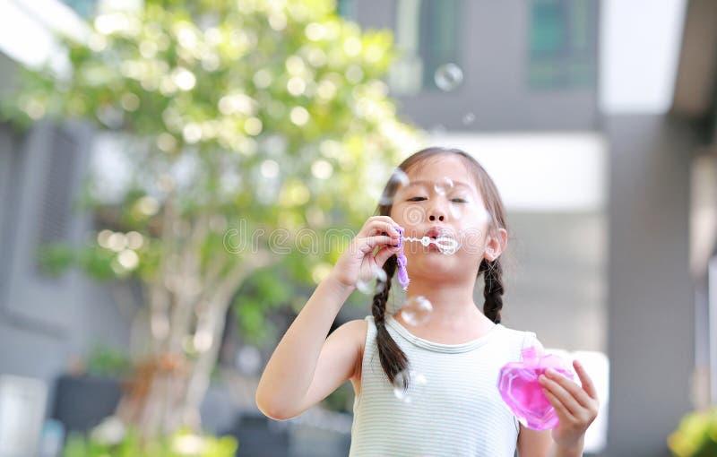 Λατρευτές φυσαλίδες λίγου ασιατικές παιδιών παιχνιδιού κοριτσιών στον κήπο υπαίθριο στοκ εικόνα