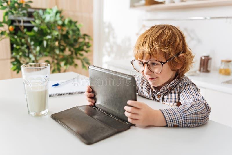 Λατρευτή ανάγνωση παιδιών κάτι στην ταμπλέτα του στοκ εικόνες
