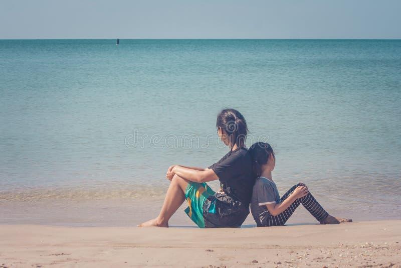 Λατρευτή και οικογενειακή έννοια: Κάθισμα γυναικών και παιδιών πλάτη με πλάτη στην παραλία άμμου στοκ φωτογραφία