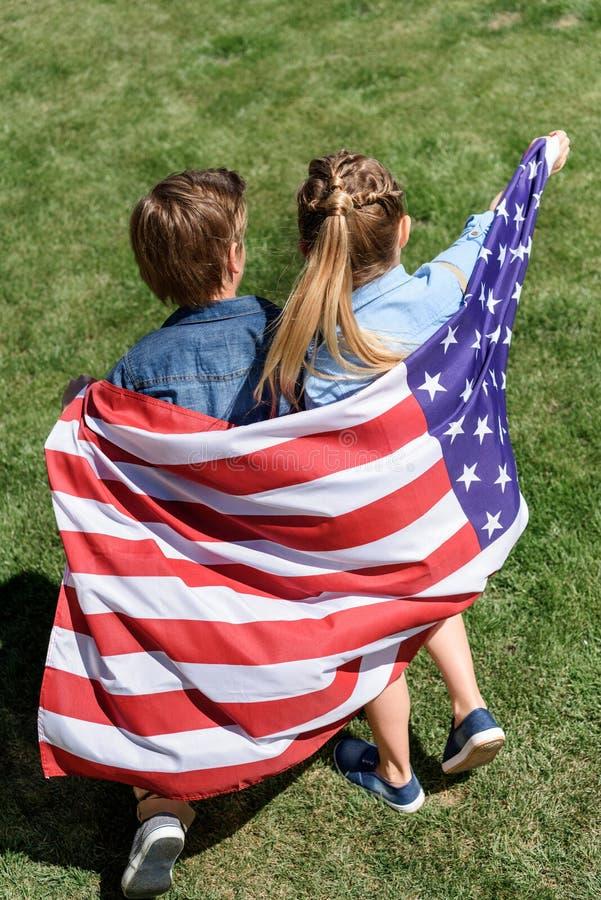 Λατρευτοί αμφιθαλείς με τη αμερικανική σημαία που έχει τη διασκέδαση υπαίθρια στοκ φωτογραφία με δικαίωμα ελεύθερης χρήσης