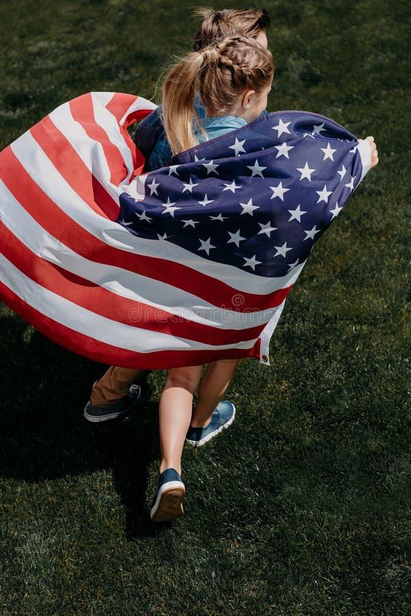 Λατρευτοί αμφιθαλείς που κρατούν τη αμερικανική σημαία και που τρέχουν υπαίθρια στοκ φωτογραφίες με δικαίωμα ελεύθερης χρήσης
