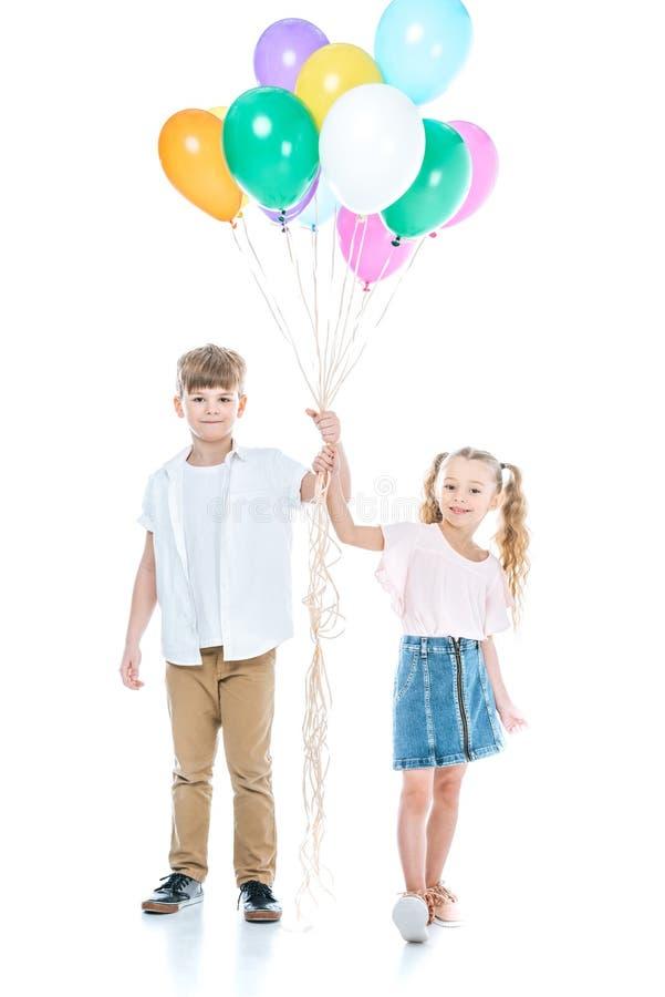 λατρευτοί ευτυχείς αμφιθαλείς που κρατούν τα ζωηρόχρωμα μπαλόνια και που χαμογελούν στη κάμερα στοκ φωτογραφίες