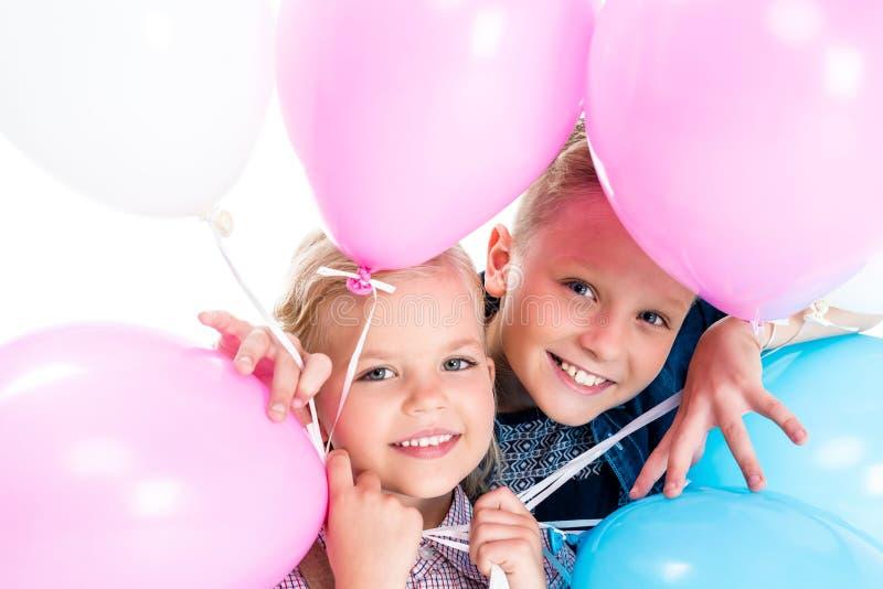 λατρευτοί ευτυχείς αμφιθαλείς που κρατούν τα μπαλόνια και που χαμογελούν στη κάμερα στοκ φωτογραφίες