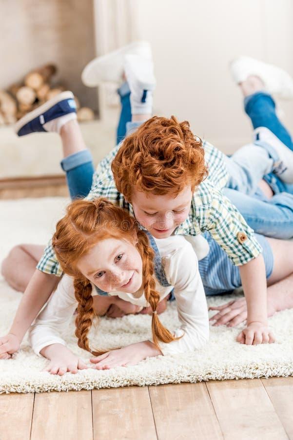 Λατρευτοί χαμογελώντας redhead αμφιθαλείς που βρίσκονται στον τάπητα και που παίζουν από κοινού στοκ εικόνα με δικαίωμα ελεύθερης χρήσης