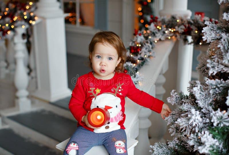 Λατρευτός λίγο ξανθό μικρό κορίτσι κοριτσιών σε ένα πουλόβερ με ένα χιόνι στοκ εικόνες