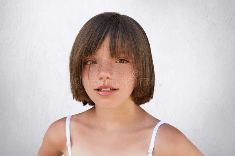Λατρευτός λίγο παιδί με τα καφετιά γοητευτικά μάτια, το φακιδοπρόσωπο δέρμα και τα λεπτά χείλια που έχουν το μοντέρνο hairdo, φορ στοκ εικόνες με δικαίωμα ελεύθερης χρήσης
