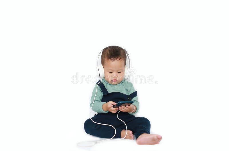 Λατρευτός Ασιάτης λίγο αγοράκι απολαμβάνεται τη μουσική ακούσματος με τα ακουστικά από το smartphone που απομονώνεται πέρα από το στοκ εικόνες
