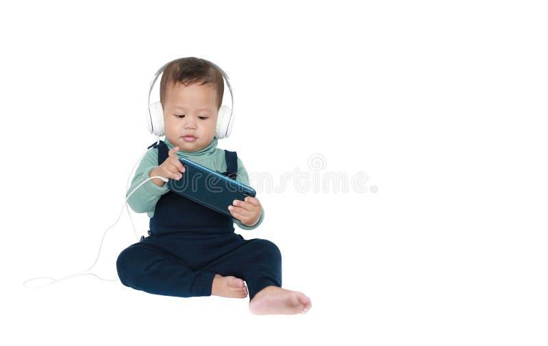 Λατρευτός Ασιάτης λίγο αγοράκι απολαμβάνεται τη μουσική ακούσματος με τα ακουστικά από το smartphone που απομονώνεται πέρα από το στοκ εικόνα
