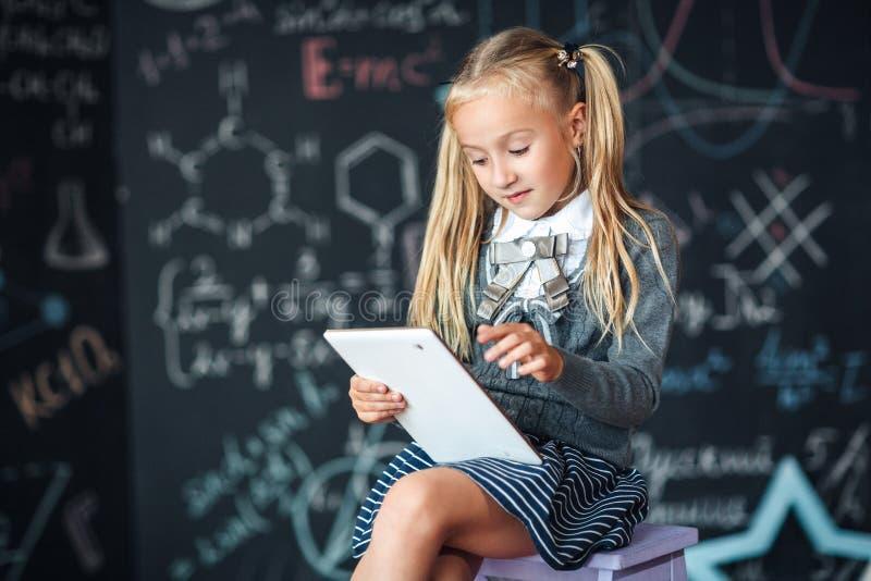 Λατρευτός λίγη ξανθή μαθήτρια στη σχολική στολή που κρατά την άσπρη ψηφιακή ταμπλέτα Πίνακας κιμωλίας με το υπόβαθρο σχολικών τύπ στοκ εικόνα