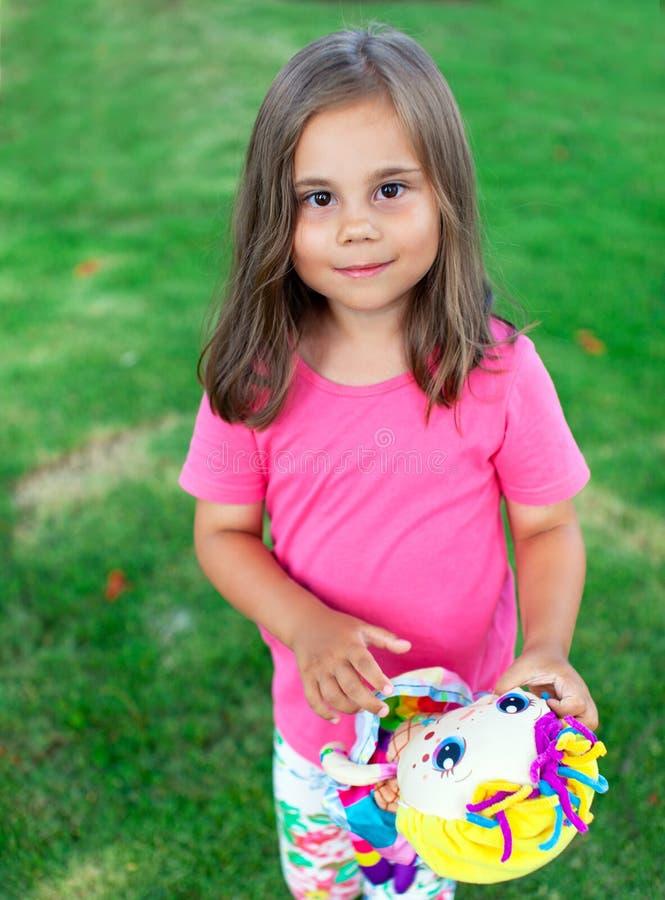 Λατρευτός λίγο κορίτσι παιδιών με μια κούκλα στα χέρια της που παίζουν στον κήπο στοκ φωτογραφίες