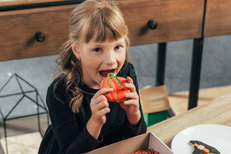 λατρευτός λίγο παιδί που τρώει το μπισκότο αποκριών και που εξετάζει τη κάμερα στοκ εικόνες