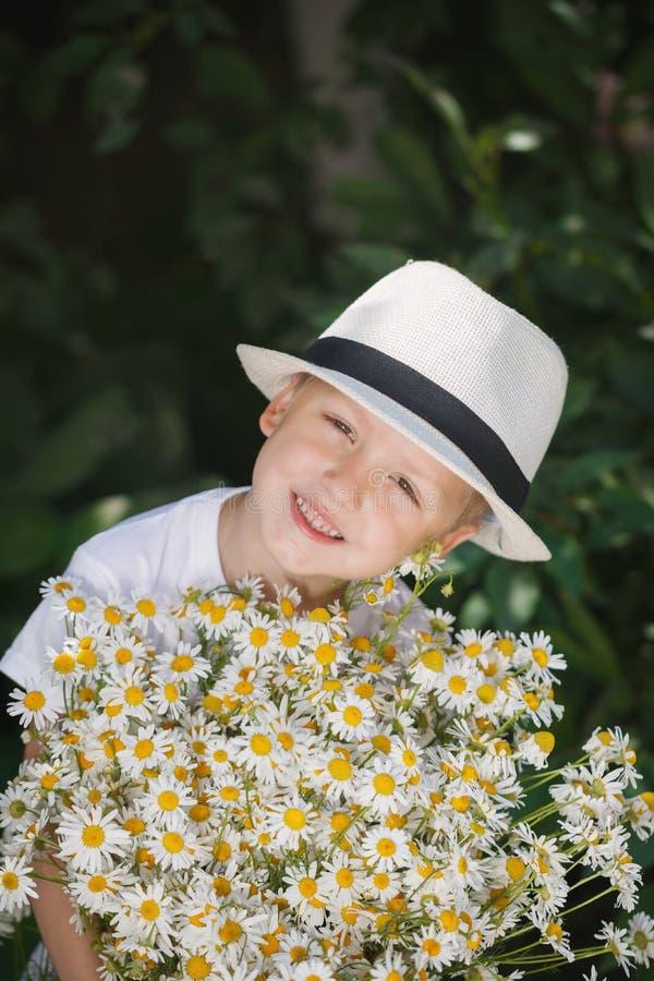 Λατρευτό αγόρι πορτρέτου σε ένα καπέλο με τη μεγάλη άσπρη ανθοδέσμη των camomiles στοκ εικόνες
