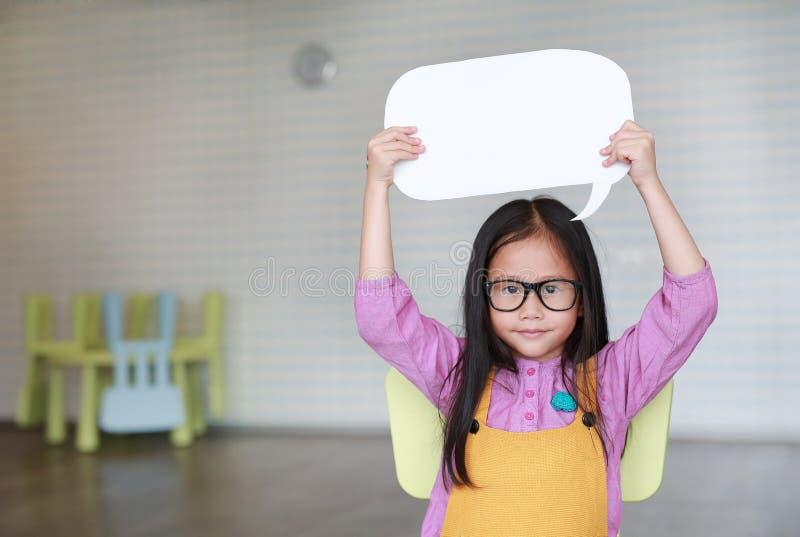 Λατρευτό ασιατικό μικρό κορίτσι που κρατά την κενή κενή λεκτική φυσαλίδα για να πει κάτι στην τάξη με το χαμόγελο και να φανεί ευ στοκ εικόνες με δικαίωμα ελεύθερης χρήσης