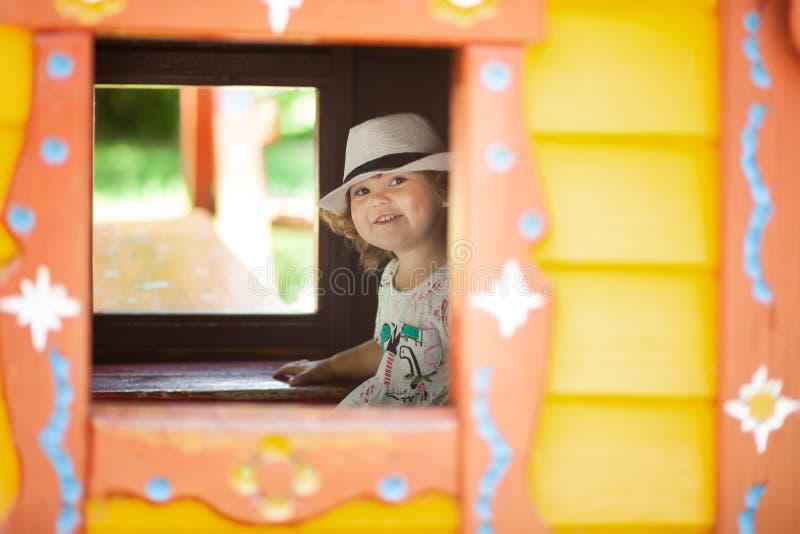 Λατρευτό αστείο παιχνίδι μικρών κοριτσιών στο σπίτι παιχνιδιών στην εσωτερική παιδική χαρά στοκ εικόνα με δικαίωμα ελεύθερης χρήσης