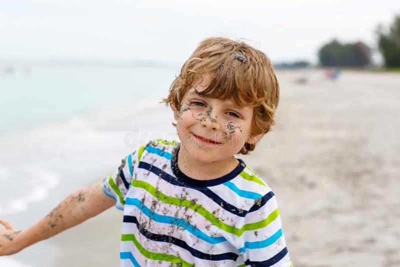 Λατρευτό ενεργό αγόρι παιδάκι που έχει τη διασκέδαση στην παραλία του Μαϊάμι, βασικό Biscayne Ευτυχής χαριτωμένη χαλάρωση, παιχνί στοκ εικόνα