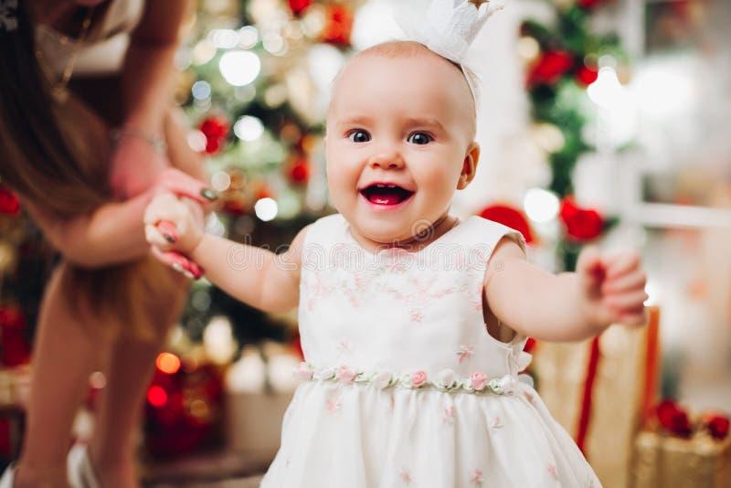 Λατρευτό ευτυχές μωρό στο εορταστικό άσπρο φόρεμα στα Χριστούγεννα στοκ φωτογραφία