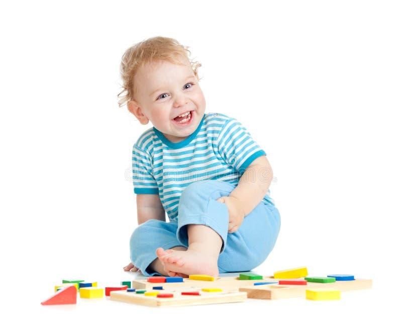 Λατρευτό ευτυχές παιδί που παίζει τα εκπαιδευτικά παιχνίδια στοκ φωτογραφία