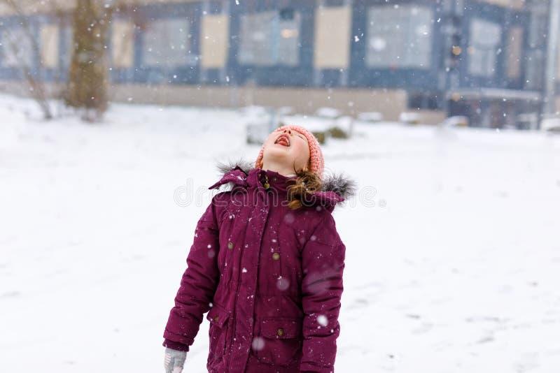 Λατρευτό κορίτσι παιδάκι στα ζωηρόχρωμα ενδύματα που παίζει υπαίθρια κατά τη διάρκεια των χιονοπτώσεων Ενεργός ελεύθερος χρόνος μ στοκ φωτογραφία με δικαίωμα ελεύθερης χρήσης