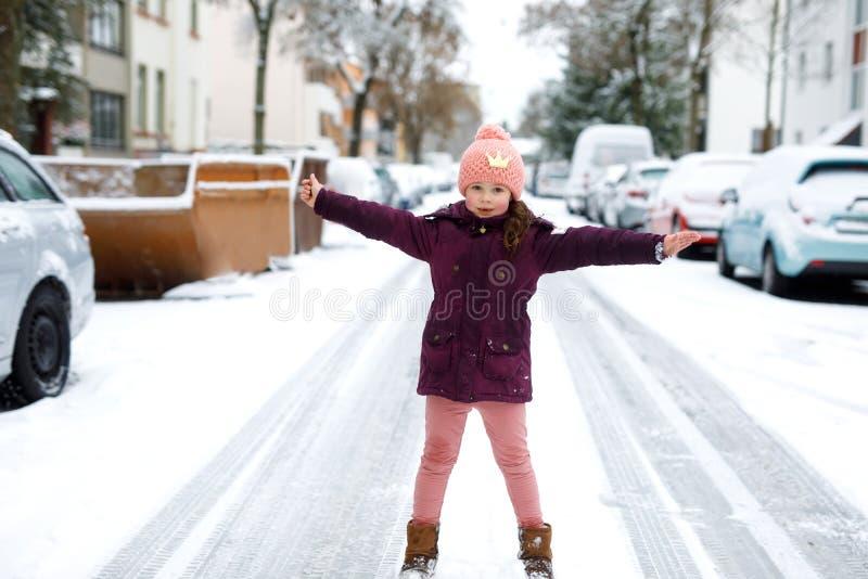 Λατρευτό κορίτσι παιδάκι στα ζωηρόχρωμα ενδύματα που παίζει υπαίθρια κατά τη διάρκεια των χιονοπτώσεων Ενεργός ελεύθερος χρόνος μ στοκ φωτογραφίες με δικαίωμα ελεύθερης χρήσης