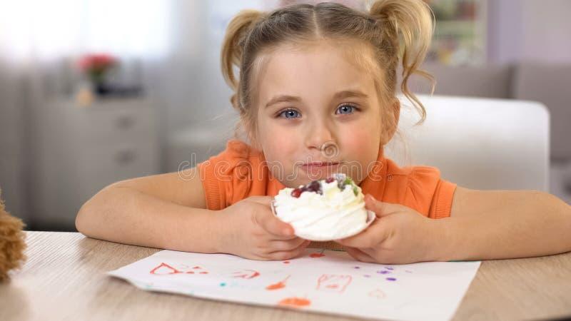 Λατρευτό κορίτσι που τρώει τη γλυκιά συνεδρίαση κέικ κρέμας στον πίνακα, ευτυχία παιδικής ηλικίας στοκ εικόνες