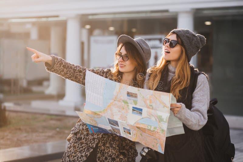 Λατρευτό κορίτσι στο γκρίζο πλεκτό καπέλο που περπατά με το φίλο γύρω από την πόλη και που κρατά το χάρτη Υπαίθριο πορτρέτο δύο π στοκ εικόνες