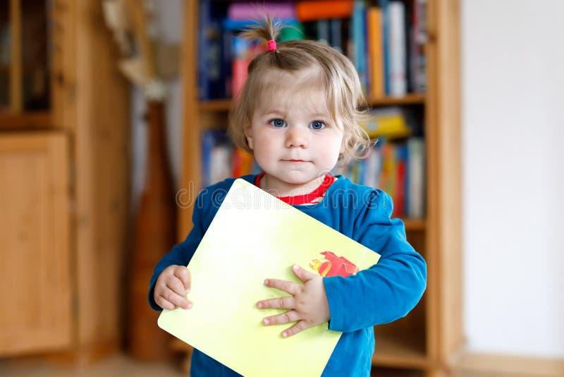 Λατρευτό κοριτσάκι που κρατά ένα βιβλίο Το όμορφο παιδί μικρών παιδιών θέλει στο σπίτι το παραμύθι στοκ φωτογραφίες