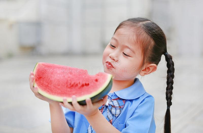 Λατρευτό λίγο ασιατικό κορίτσι παιδιών στη σχολική στολή απολαμβάνει το καρπούζι στοκ εικόνα