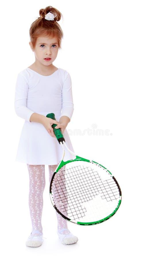 Λατρευτό μικρό κορίτσι με μια ρακέτα αντισφαίρισης υπό εξέταση στοκ εικόνες