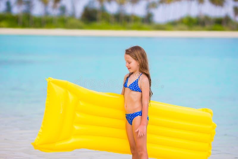 Λατρευτό μικρό κορίτσι με το διογκώσιμο στρώμα αέρα κατά τη διάρκεια των διακοπών παραλιών στοκ φωτογραφία